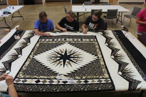 Quilting a black and gold Mariner's Compass quilt.