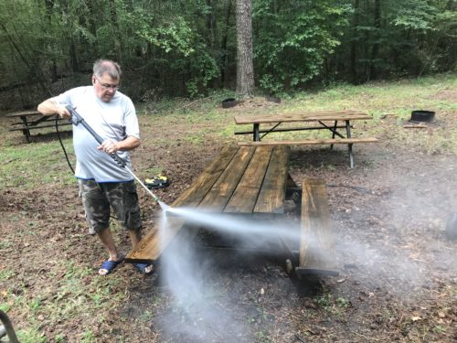 Keith Graybill pressure washes one of many picnic tables.